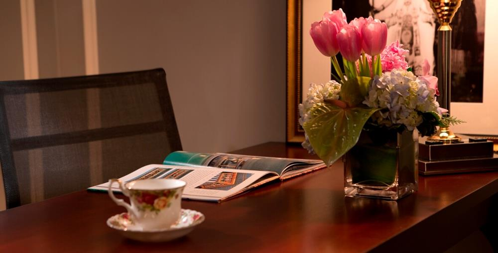 Desk with flowers, tea and magazine at Millennium Biltmore Hotel Los Angeles